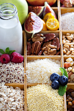 Breakfast items in wooden box with grains and berries