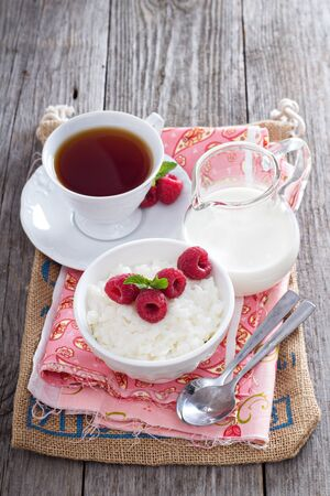 Rice pudding with raspberries and tea for breakfast