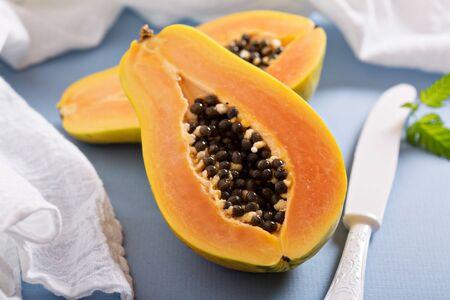 Cut papaya exotic fruit on a blue table Stock Photo