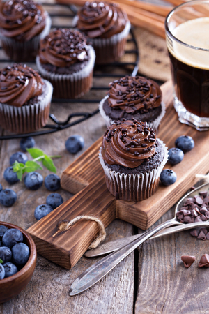 Coffee and chocolate cupcakes on wooden table