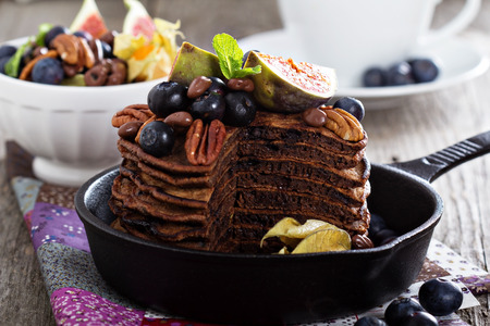 chocolate sauce: Stack of chocolate pancakes decorated with berries