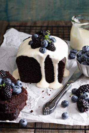 frosting': Chocolate loaf cake sliced decorated with frosting and berries Stock Photo