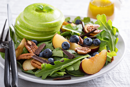Fresh healthy salad with leafy greens, plums, nuts and apple