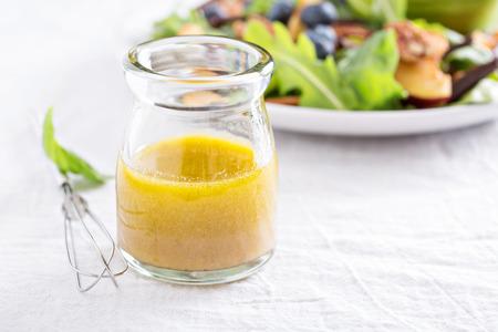 Aderezo para ensaladas con aceite de oliva, la miel, la mostaza y el vinagre Foto de archivo - 45656596