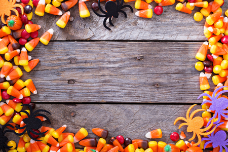 candy background: Halloween candy frame around rustic board empty space for your text Stock Photo