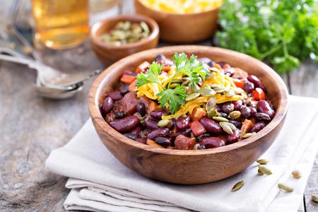 Vegetarische chili met rode en zwarte bonen, cheddar en pompoenpitten