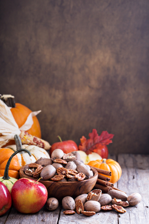 brown background: Pumpkins, nuts, indian corn and apples on a rustic table Stock Photo