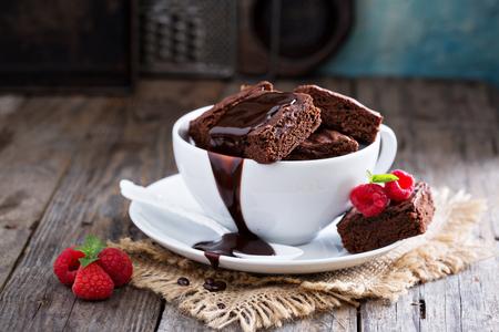 porcion de torta: Brownies en las tazas de café apiladas con salsa de chocolate con chocolate caliente