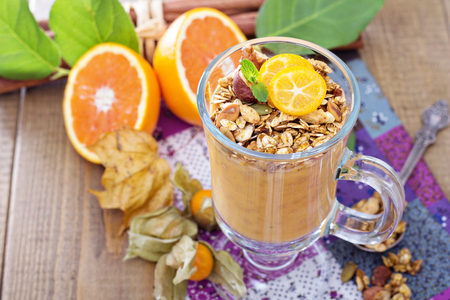 glass topped: Pumpkin smoothie topped with pumpkin granola for breakfast