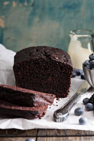 Chocolate loaf cake sliced decorated with frosting and berries 스톡 콘텐츠