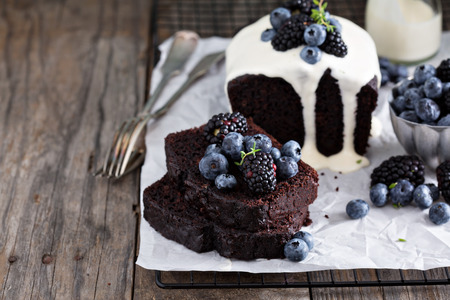 Chocolate loaf cake sliced decorated with frosting and berries Archivio Fotografico