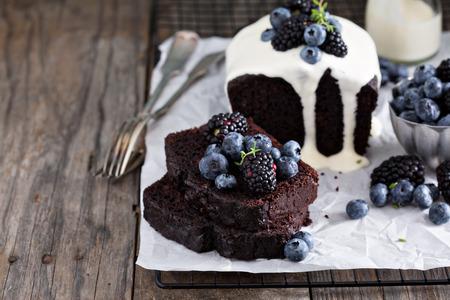 porcion de torta: Torta de pan de chocolate en rodajas decorado con crema de vainilla y bayas