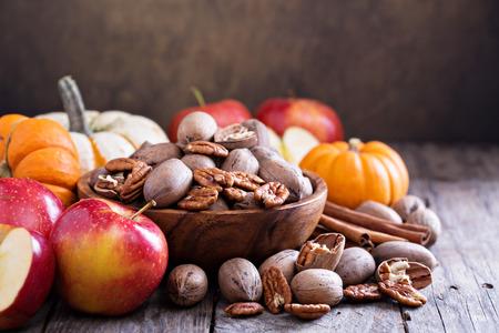 Pompoenen, noten, maïs en appels op een rustieke tafel