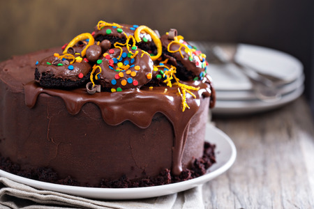 Dark chocolate orange cake with ganashe frosting decorated with mini donuts Stock Photo