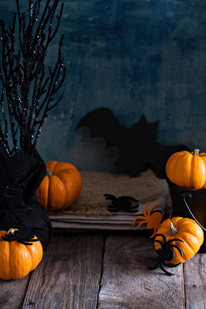 Little pumpkins on Halloween decorated table with spiders and bat