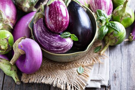 Eggplants of different color and variety on the table Imagens