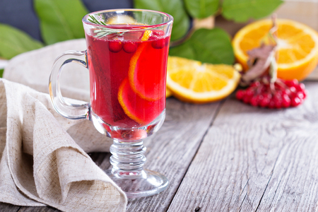 Cranberry orange punch with cinnamon and rosemary in a glass