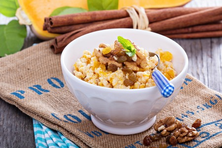 Pumpkin and millet porridge served with nuts and raisins Banco de Imagens