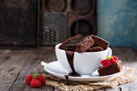 galleta de chocolate: Brownies en las tazas de caf� apiladas con salsa de chocolate con chocolate caliente