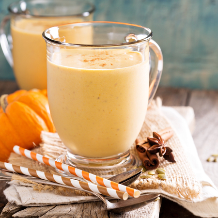 orange yellow: Healthy pumpkin smoothie in big mugs on rustic background Stock Photo
