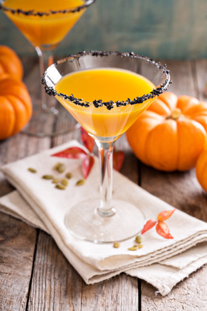 vermouth: Pumpkintini pumpkin martini coctail with black salt rim for fall and halloween parties Stock Photo