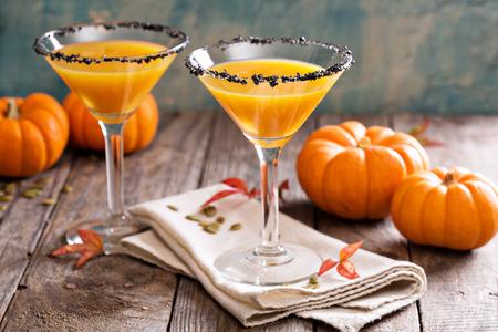 Pumpkintini pumpkin martini coctail with black salt rim for fall and halloween parties Archivio Fotografico
