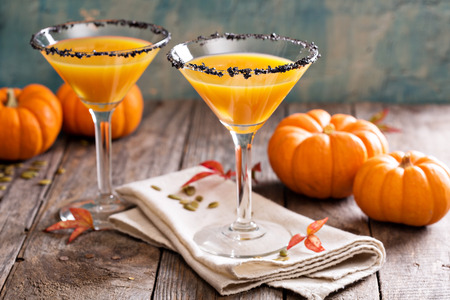 halloween: Pumpkintini pumpkin martini coctail with black salt rim for fall and halloween parties Stock Photo