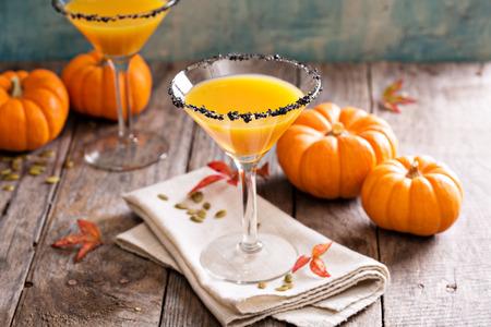 martini glasses: Pumpkintini pumpkin martini coctail with black salt rim for fall and halloween parties Stock Photo
