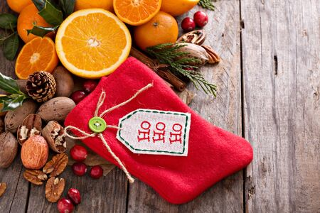 pinoli: Winter and christmas ingredients still life with oranges, cranberry, nuts and spices and a decorative stocking Archivio Fotografico