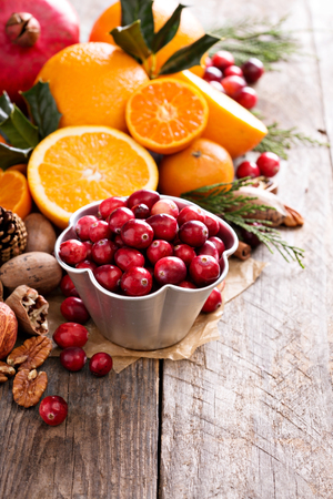 holiday decor: Fall and winter ingredients still life with oranges, cranberry, nuts and spices