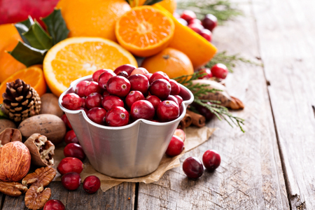 brown background: Fall and winter ingredients still life with oranges, cranberry, nuts and spices