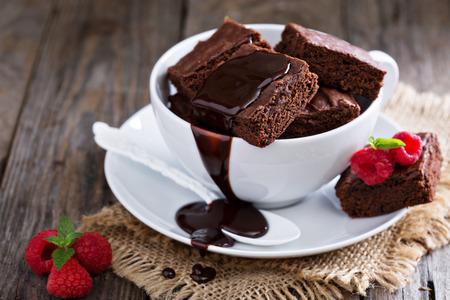 rebanada de pastel: Brownies en las tazas de café apiladas con salsa de chocolate con chocolate caliente