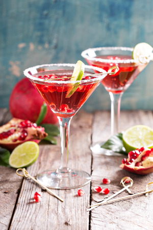 martini glass: Pomegranate martini with slices of lime and pomegranate seeds Stock Photo