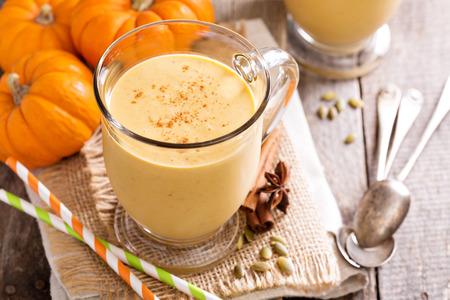 large pumpkin: Healthy pumpkin smoothie in big mugs on rustic background Stock Photo