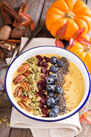pecans: Pumpkin smoothie bowl with chia seeds, pecans, cranberries and blueberries Stock Photo