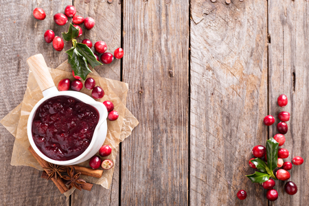 Cranberry sauce in ceramic saucepan on dark background
