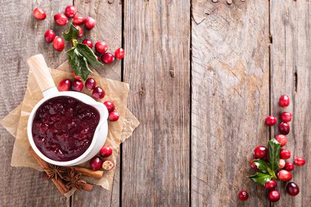arandanos rojos: Salsa de arándano en una olla de cerámica en el fondo oscuro