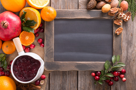 Fall and winter ingredients background with chalkboard, oranges, cranberry, nuts and spices