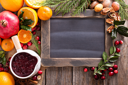 Christmas ingredients background with chalkboard, oranges, cranberry, nuts and spices