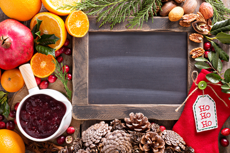 christmas spices: Christmas ingredients background with chalkboard, oranges, cranberry, nuts and spices