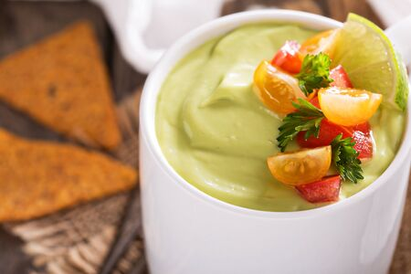 chips and salsa: Cold avocado soup with tomato and herb salsa and tortilla chips Stock Photo
