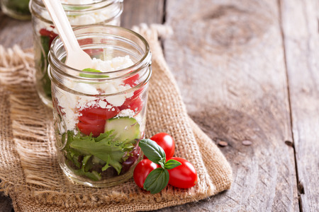 salad with tomatoes, green leafs and feta cheese in mason jars