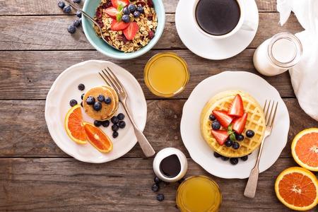 prima colazione: Tavolo per la colazione con cialde, muesli e bacche fresche