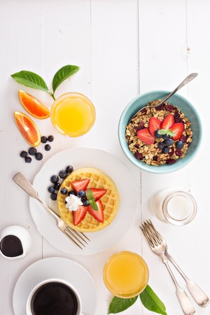 food on table: Breakfast table with waffles, granola and fresh berries