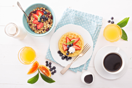 breakfast coffee: Breakfast table with waffles, granola and fresh berries