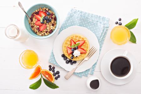 Table de petit déjeuner avec des gaufres, céréales et fruits frais