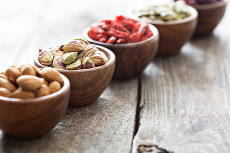 Variety of nuts and dried fruits in small wooden bowls