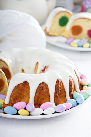 Easter cake with colorful filling, glaze and decorative egg candies Stock Photo