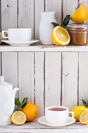 breakfast cup: Tea with citrus fruits on the shelf of white cupboard