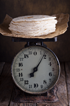 tortillas: Stack of wheat tortillas on old vintage kitchen scales Stock Photo